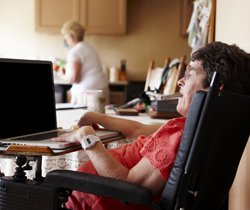 disabled woman working on laptop at home